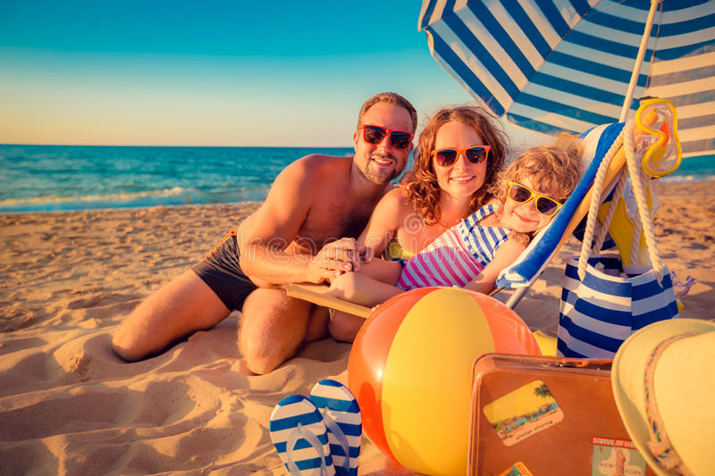 Happy family on the beach. Happy family sitting on the sunbed. Man, women and child having fun at the beach. Summer vacation concept