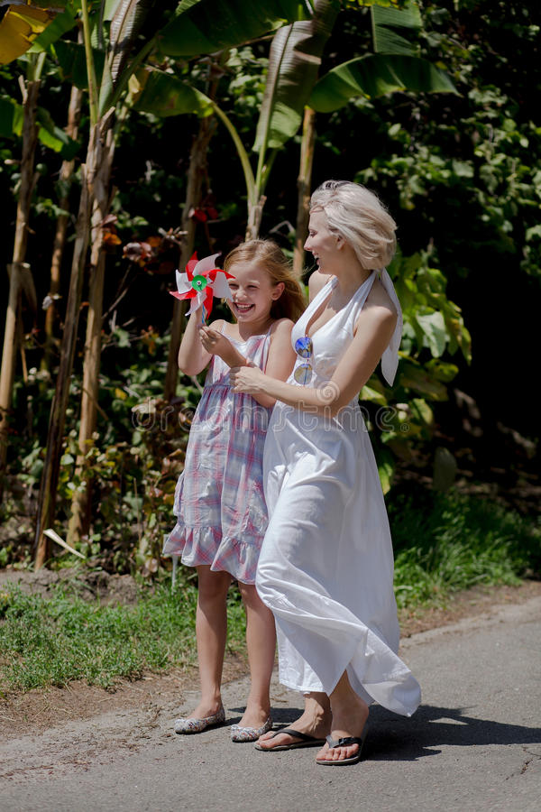 Happy family, beautiful mom and daughter walking, playing in park. royalty free stock photography