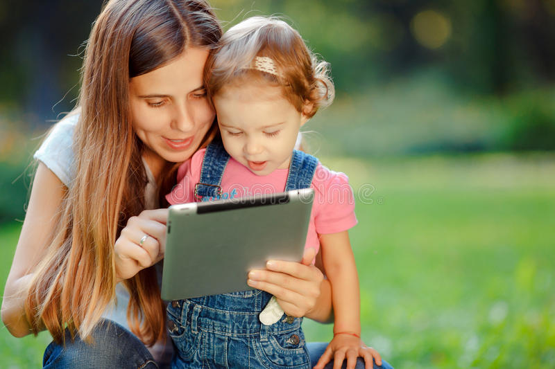 Happy family. Beautiful mother and kid girl playing at tablet pc outdoors in fall. Happy mother showing her daughter funny pictures your tablet. Happy family stock photos