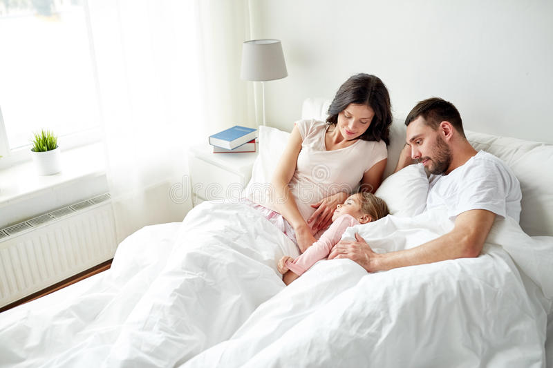 Happy family in bed at home stock photography