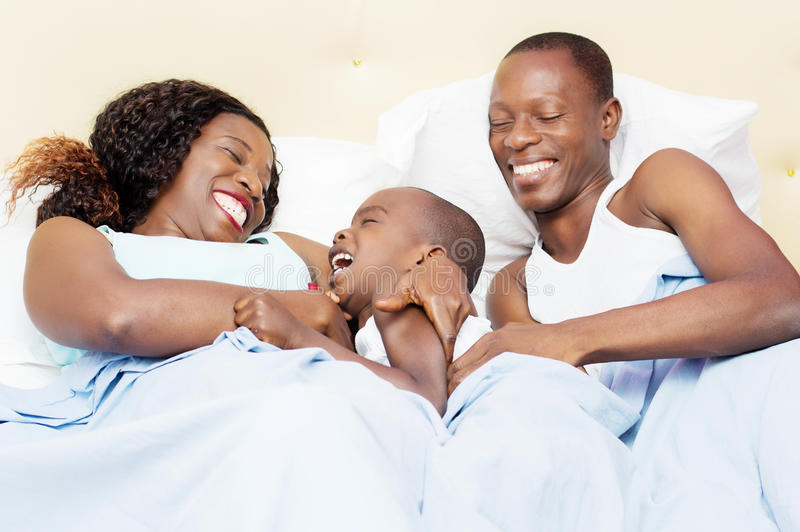 Happy family in bed stock photos