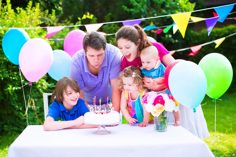Happy family at birthday party. Happy big family with three kids - school age boy, toddler girl and a little baby enjoying birthday party with a cake blowing stock photo