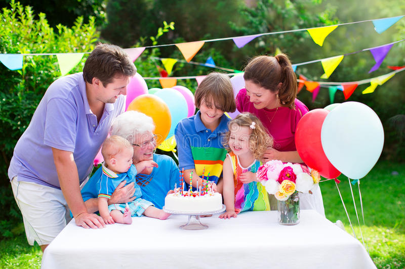 Happy family at a birthday party. Happy big family - young parents, grandmother and three kids, teenage boy, toddler girl and little baby celebrating birthday stock photography