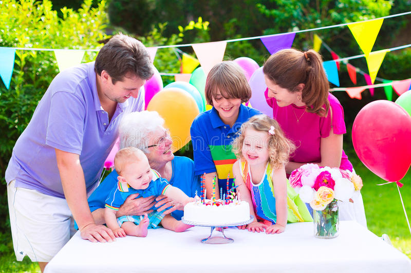 Happy family at a birthday party. Happy big family - young parents, grandmother and three kids, teenage boy, toddler girl and little baby celebrating birthday royalty free stock image