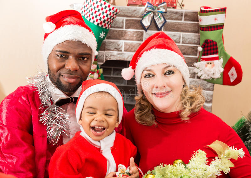 Happy family: black father, mom and baby boy dressed costume Santa Claus by fireplace. Christmas and New Year stock photography