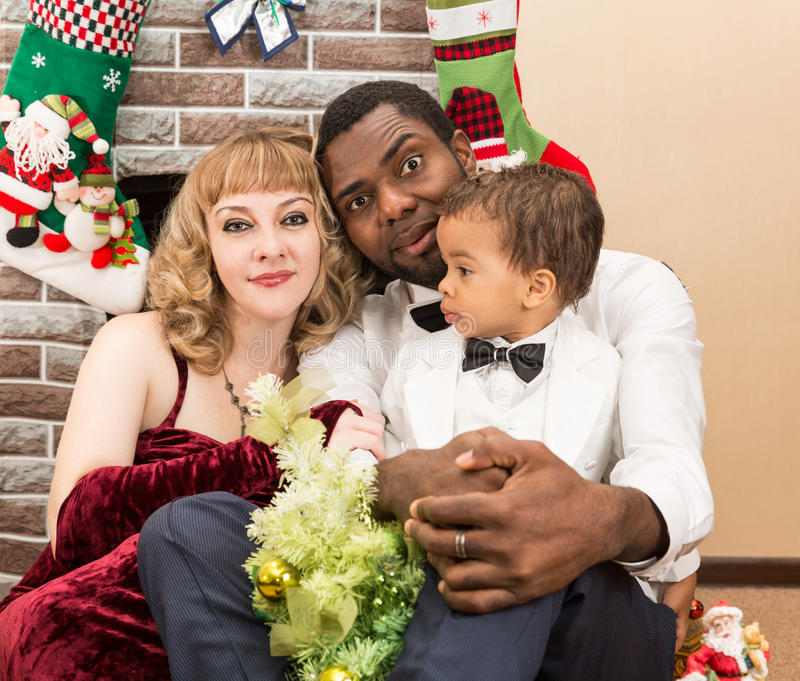 Happy family: black father, mom and baby boy by fireplace. Christmas. And New Year royalty free stock photography