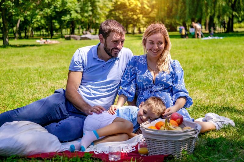 Happy family on the blanket resting in the park, pregnant mother. stock photo