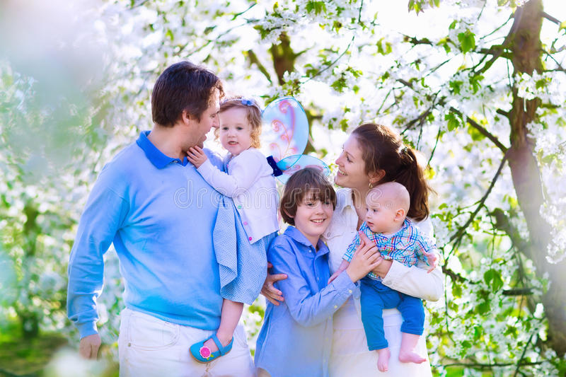 Happy family in a blooming cherry tree garden royalty free stock images