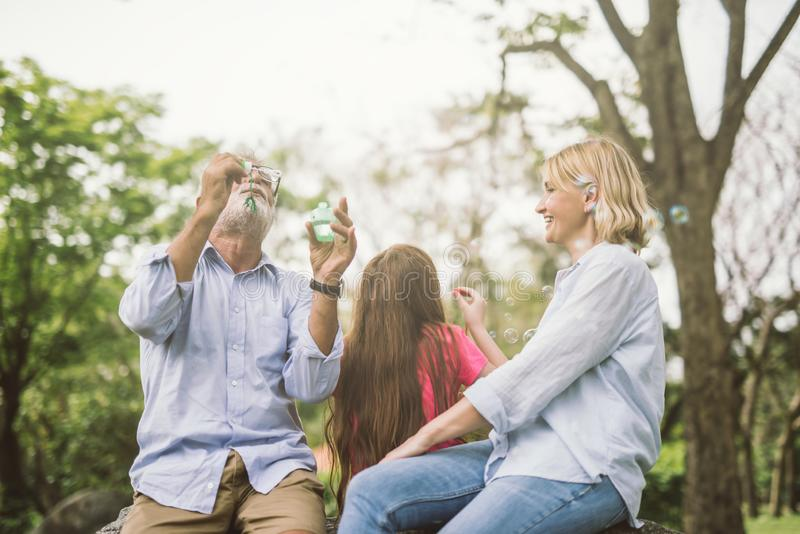 Happy family blow soap bubbles in park. Happy family blow soap bubbles in park royalty free stock image