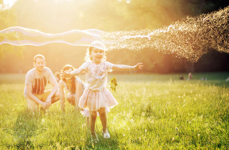 Happy family blowing a bubbles in a spring park stock image