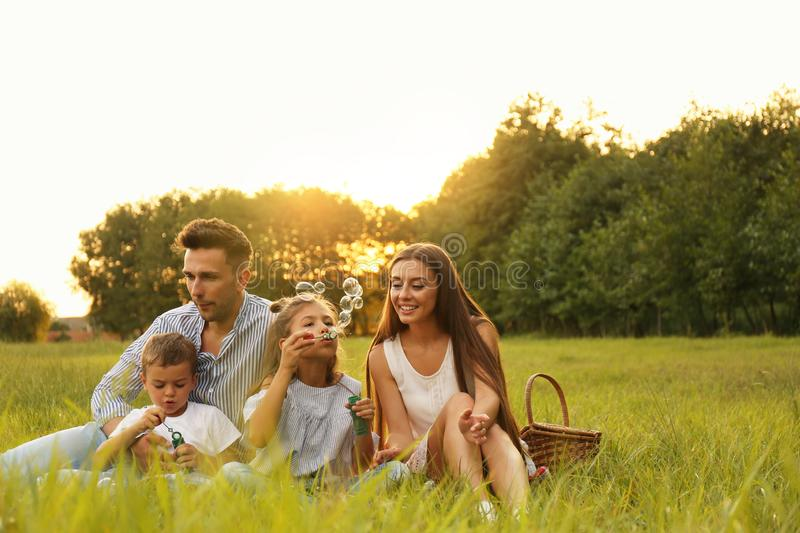 Happy family blowing soap bubbles in park at sunset. Summer picnic stock images