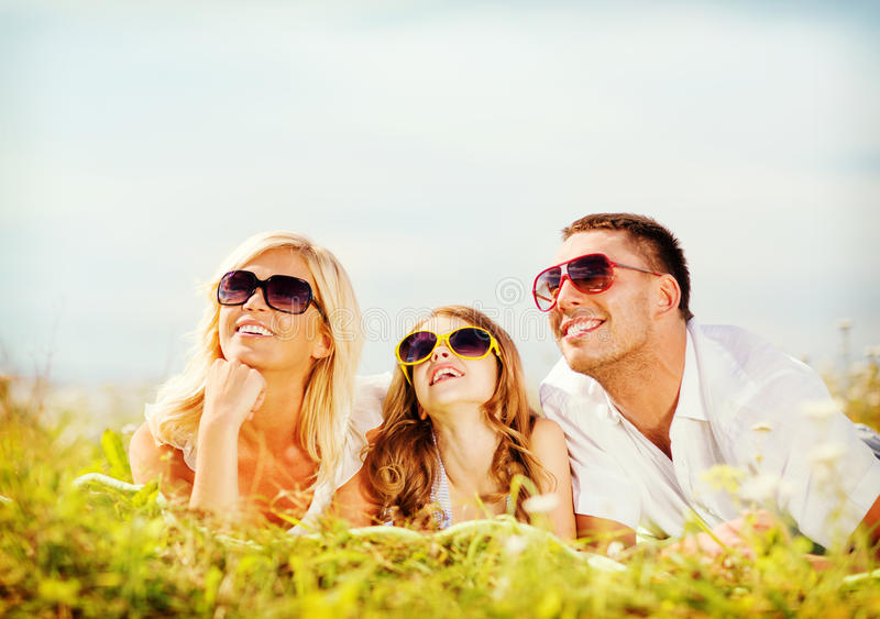 Happy family with blue sky and green grass. Summer holidays, children and people concept - happy family with blue sky and green grass royalty free stock image