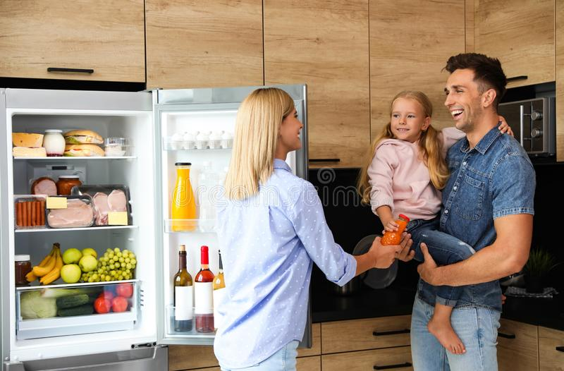 Happy family with bottle of juice near refrigerator. In kitchen stock photography