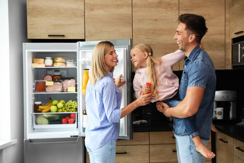 Happy family with bottle of juice near refrigerator. In kitchen stock images