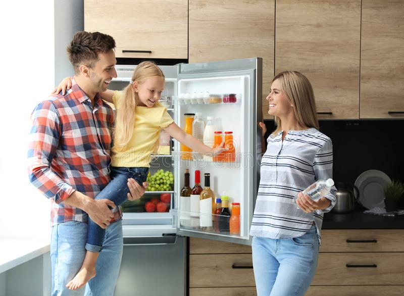 Happy family with bottle of water near refrigerator. In kitchen stock images