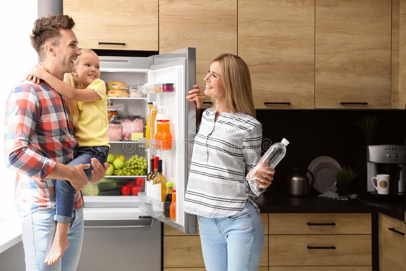 Happy family with bottle of water near refrigerator royalty free stock images