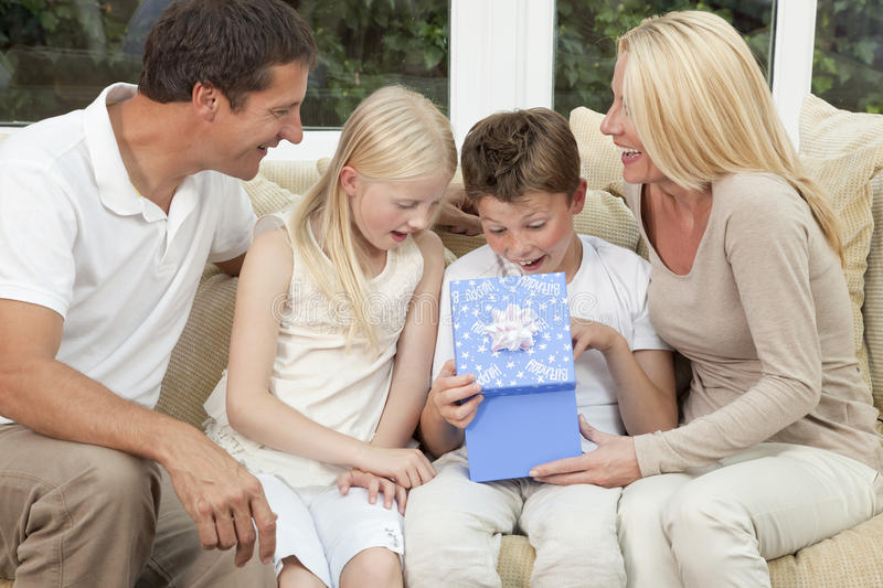 Happy Family Boy Child Opening Birthday Present. An attractive happy, family of mother, father, son and daughter sitting on a sofa at home the boy child is royalty free stock photography