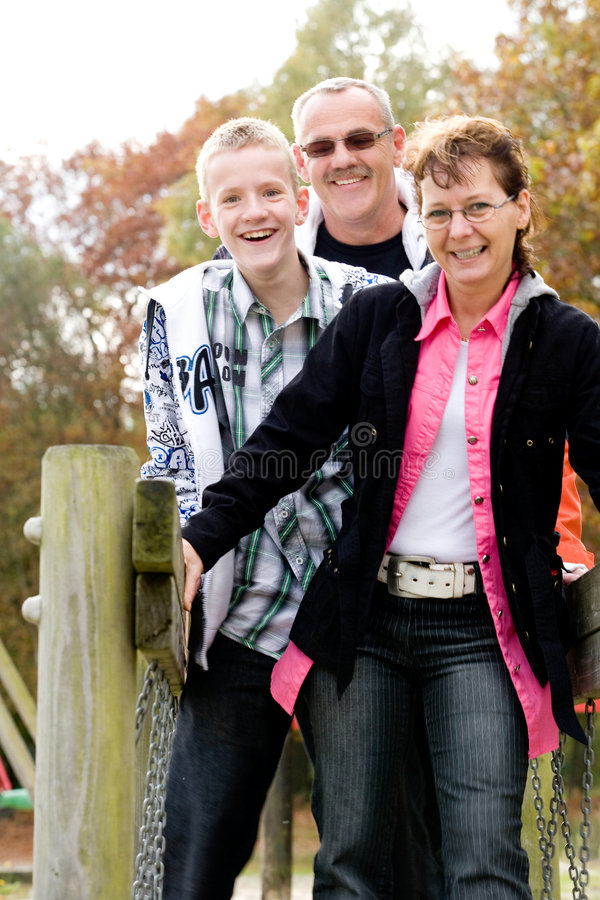 Happy family on the bridge. Happy young family on the bridge on the playground royalty free stock photography