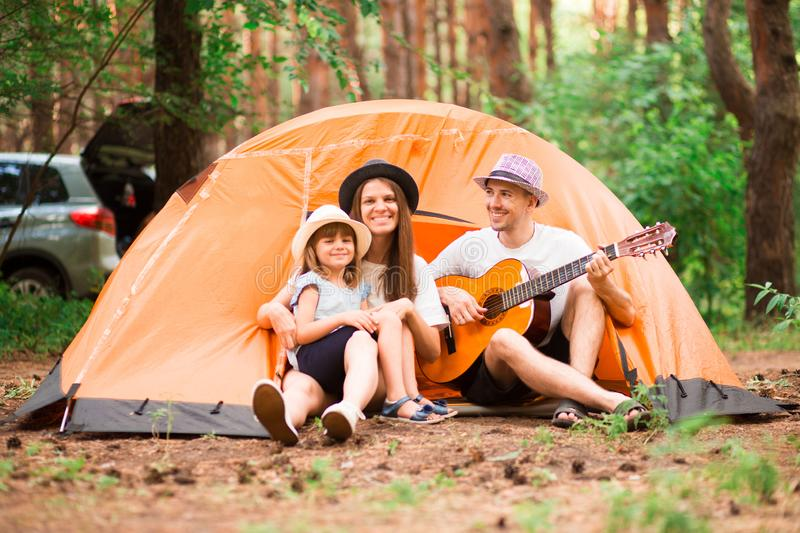 Happy family camping in forest, playing guitar and singing song together in front of tent. Concept of family. stock photos