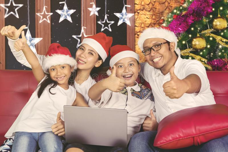 Happy family celebrates Christmas day with laptop. Picture of happy family showing thumbs up while celebrating Christmas day with a laptop at home stock photos