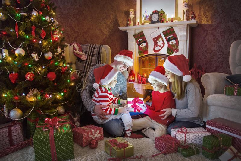 Happy family celebrating Christmas. Near the fireplace under the Christmas tree royalty free stock photo