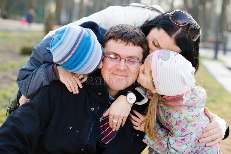 Happy family of 4 celebrating: Parents with two children having fun hugging & kissing father who is happy smile, closeup portrait royalty free stock image