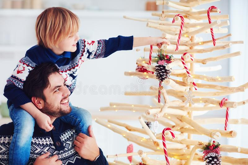 Happy family, father and son decorate handcrafted christmas tree made of driftwood at home royalty free stock photos