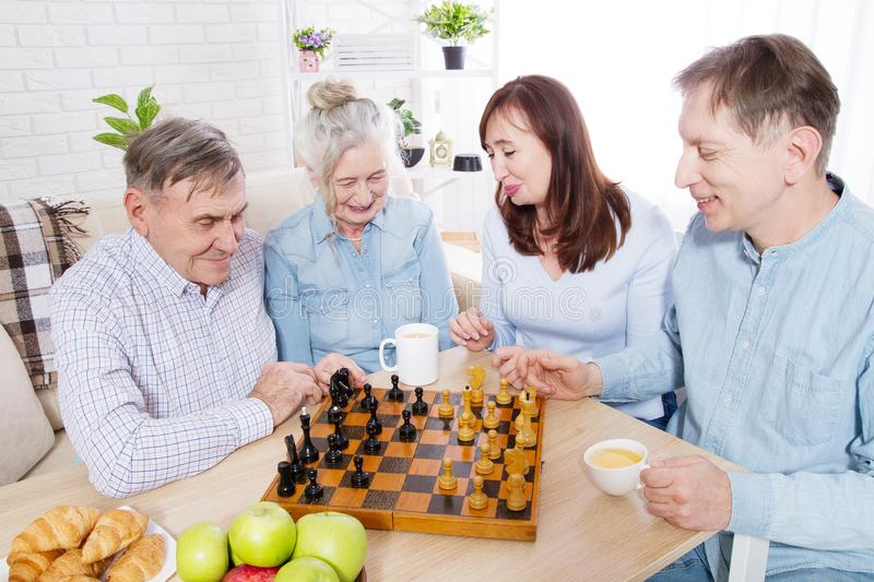 Happy family chess game time at nursing home for elderly. Parents with children have fun talk and leisure. Senior couple stock photo