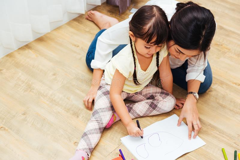 Happy family child kid girl kindergarten drawing teacher education mother mom with beautiful mother. At interior room home royalty free stock photography