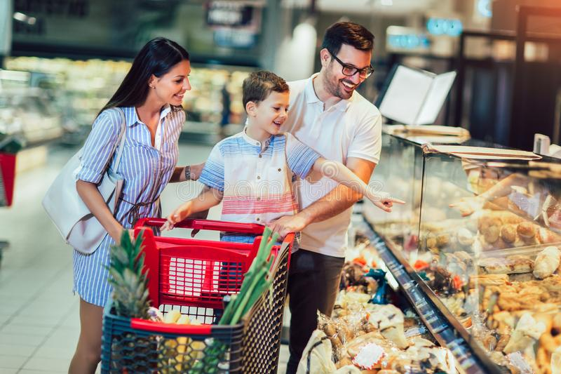 Family with child and shopping cart buying food at grocery store or supermarket stock photography