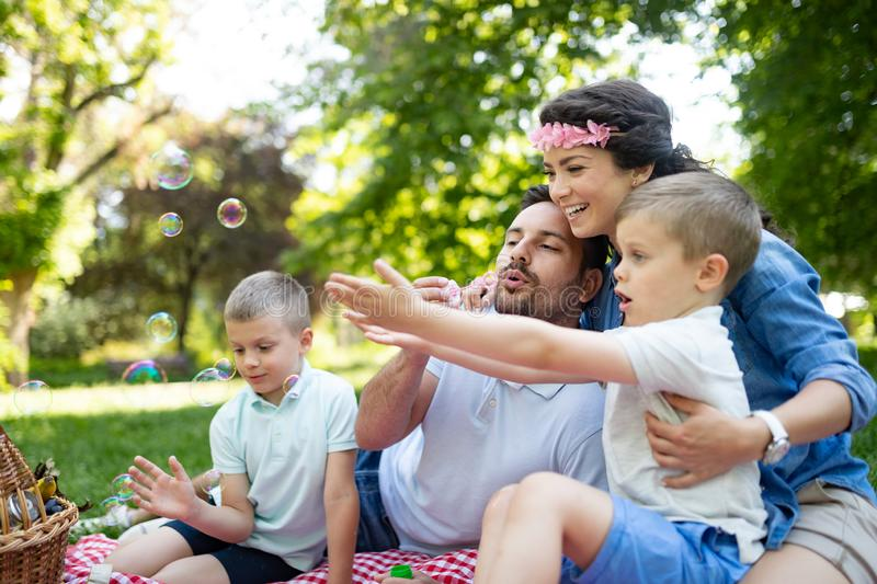 Family with children blow soap bubbles outdoors. Happy family with children blow soap bubbles outdoor stock image