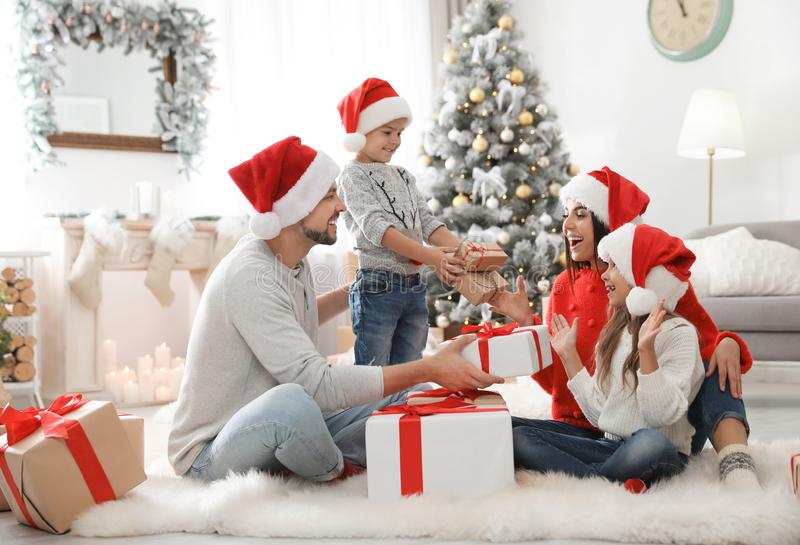 Happy family with children and Christmas gifts on floor. At home stock image