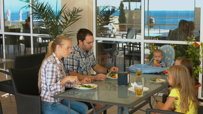 Happy family with children having lunch in a cafe royalty free stock photos