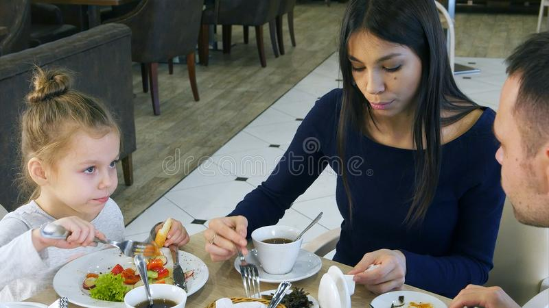 Happy family with daughter having lunch in a cafe stock photos