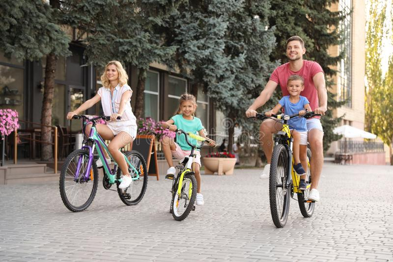 Happy family with children riding bicycles city. Happy family with children riding bicycles in city stock photos