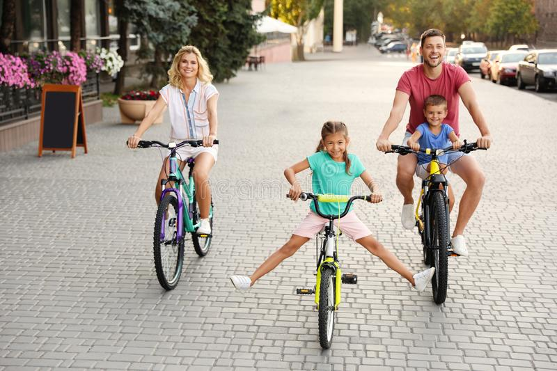 Happy family with children riding bicycles stock photography