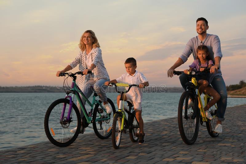 Happy family with children riding bicycles near river. At sunset stock images