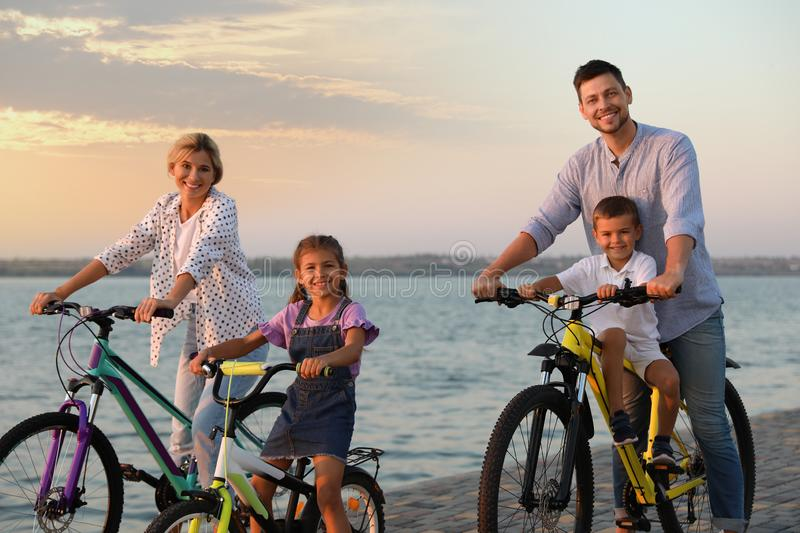 Happy family with children riding bicycles near river stock photos