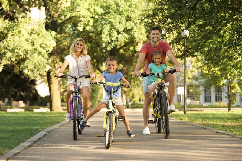 Happy family with children riding bicycles stock photos