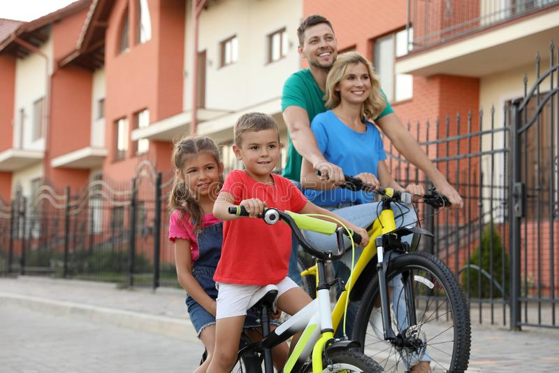 Happy family with  riding bicycles on street. Happy family with children riding bicycles on street royalty free stock images