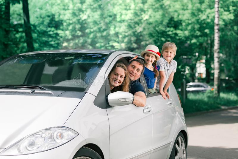 Happy family with children sitting in a family car royalty free stock photography