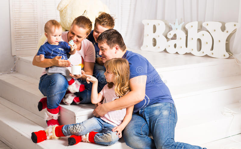 Happy family with 3 children sitting on floor of living room at home royalty free stock photography