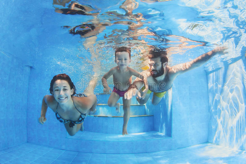 Happy family with children swimming with fun in pool stock images