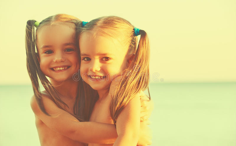 Happy family children twin sisters on the beach royalty free stock photography