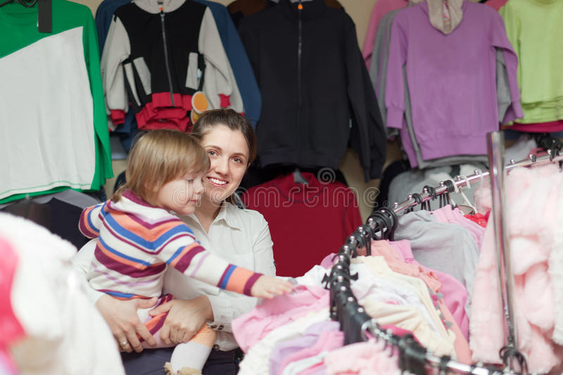 Happy family chooses wear at clothes shop stock photo