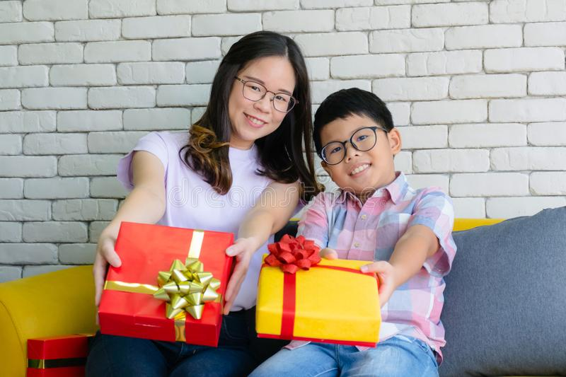 Happy family in christmas festival. Mom and son with gifts box on the background of the Christmas interior and gifts. Merry Christ royalty free stock images