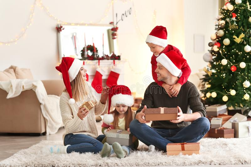 Happy family with Christmas gifts at home stock photo
