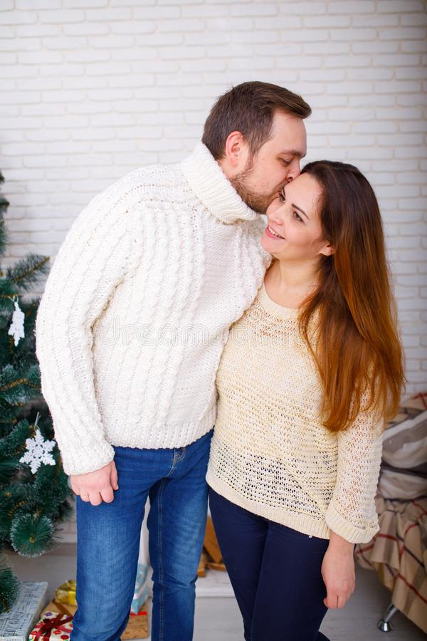 Happy family at Christmas in the house near the Christmas tree, the guy kisses his girlfriend. stock images