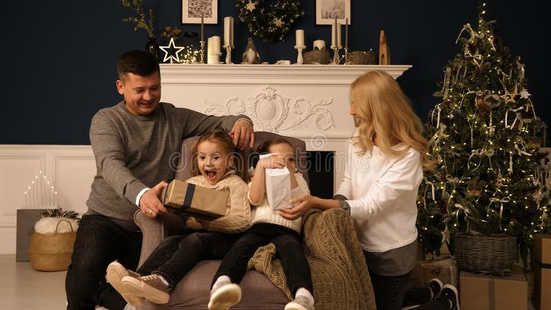 Happy family on Christmas morning at the Christmas tree with gifts. Professional shot in 4K resolution. 015. You can use it e.g. in your christmas, commercial stock photography
