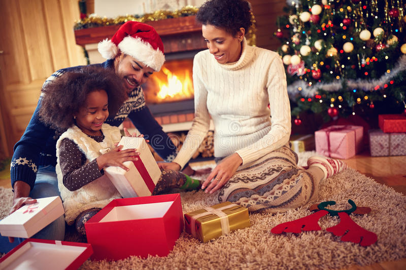 Happy family in Christmas morning opening present. In home front of Christmas tree royalty free stock photos
